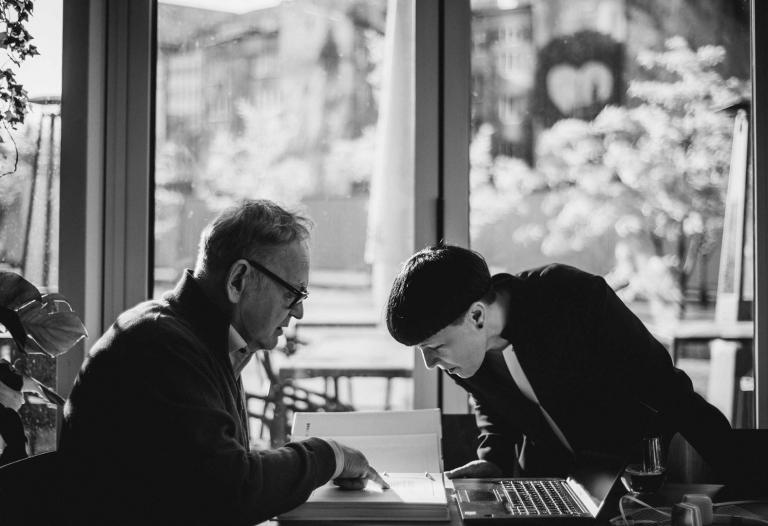 starszy mężczyzna i młoda kobieta czytają zapiski w segregatorze