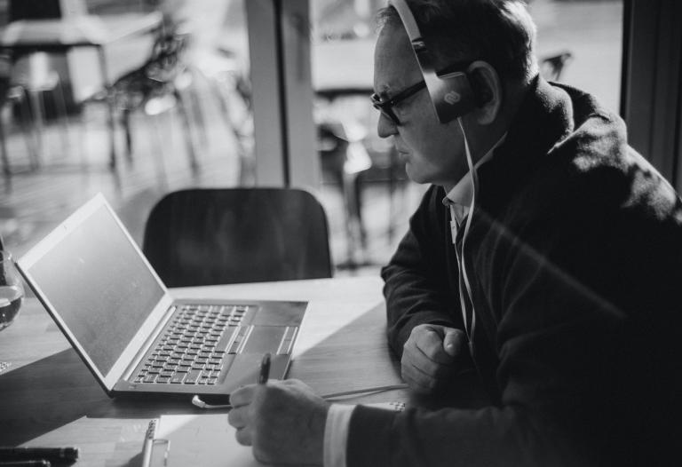 Leszek Greń w słuchawkach odtwarza na laptopie