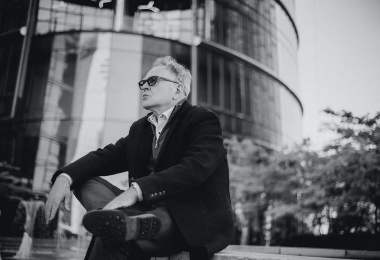 Leszek Greń siedzi oprzed przeszklonym budynkiem